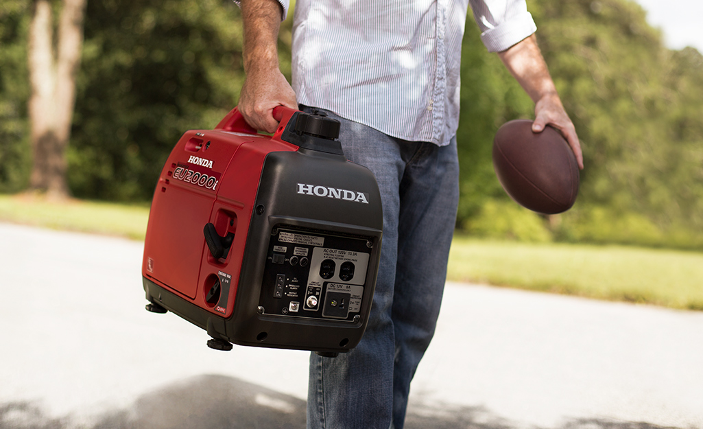 A man carries a generator in one hand and a football in the other.