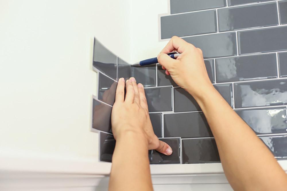 A Person Lays Bathroom Tile
