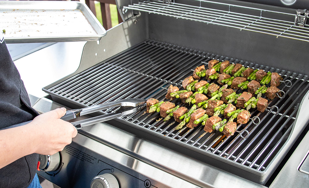 A person uses grilling tongs to rotate kebabs on a gas grill.