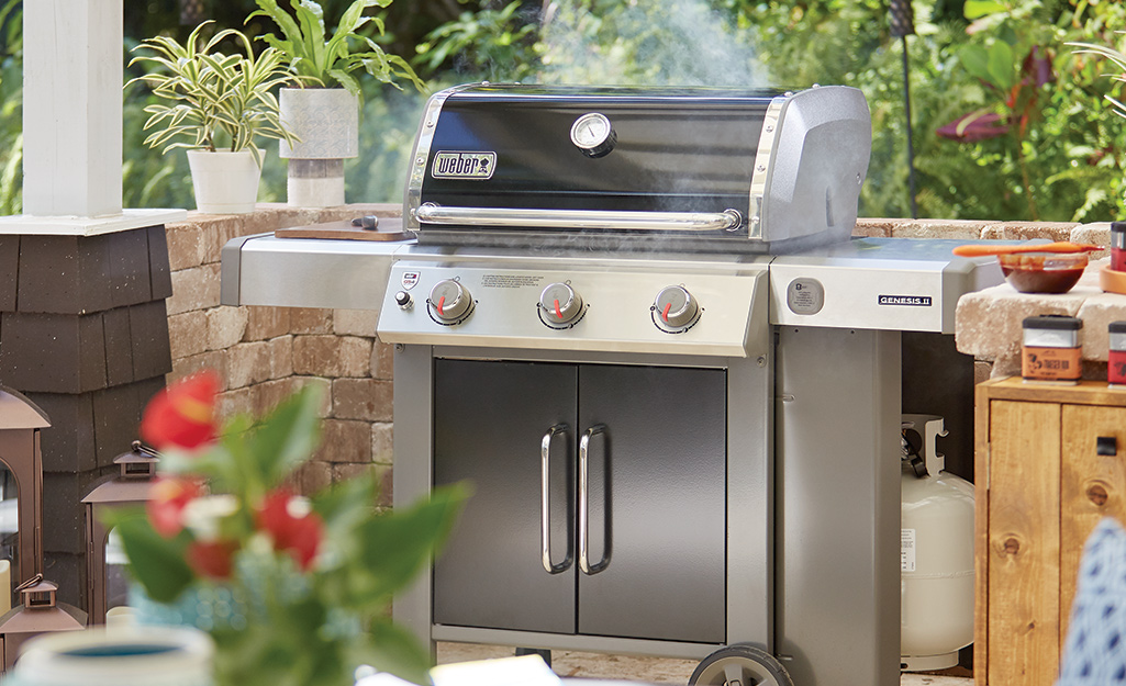 A propane grill on a patio.