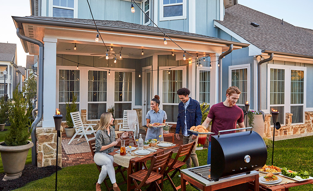 Four friends gather in a backyard around a grill and outdoor seating for a cookout.