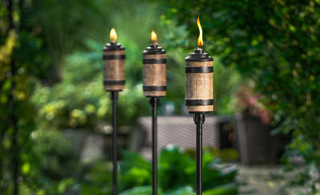 Three lit garden torches in a backyard space.
