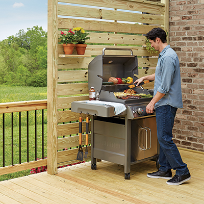 A man cooks food on a grill on a patio.