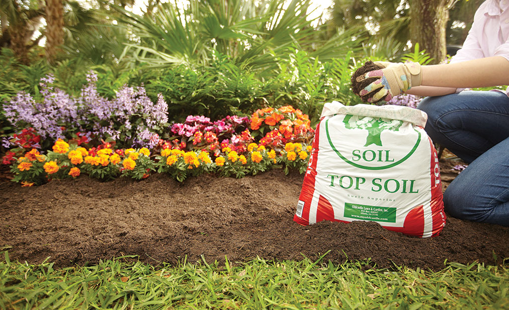 Someone kneeling beside a border of marigolds and other flowers and adding top soil.