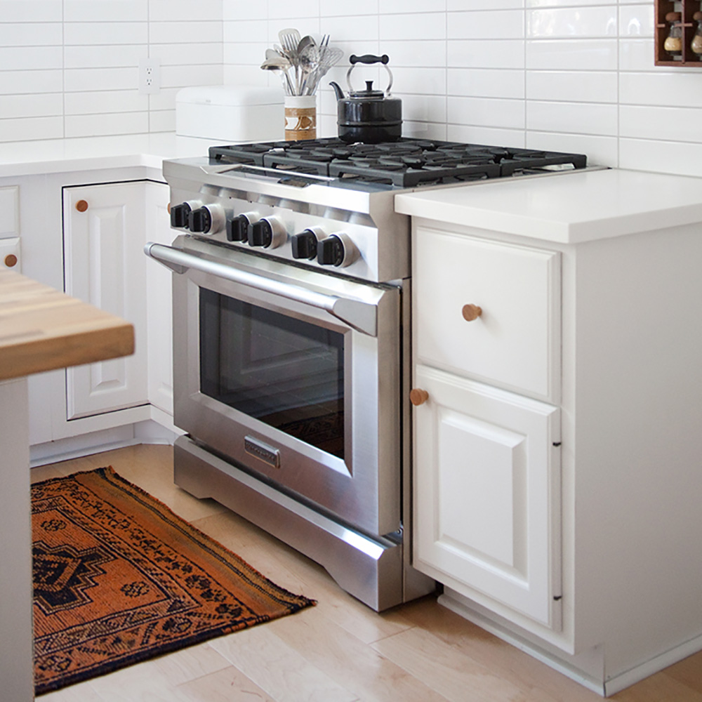 A white kitchen with a stainless steel KitchenAid range.