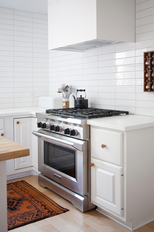 A stainless steel KitchenAid gas range in a white kitchen.