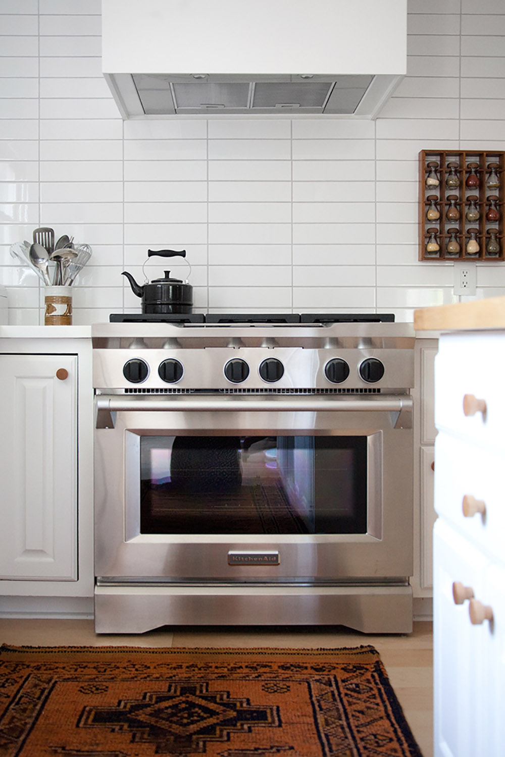 A contemporary Whirlpool hood vent surrounded by a white vent cover.