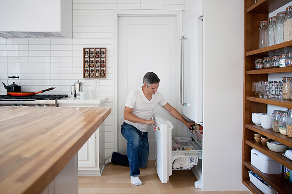 A man leans down to pull out a drawer in a bottom freezer.