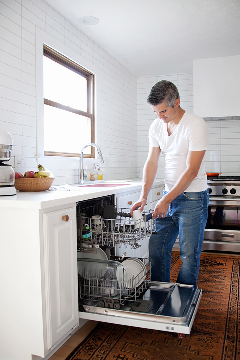A man adds a cup to the top rack of a dishwasher.