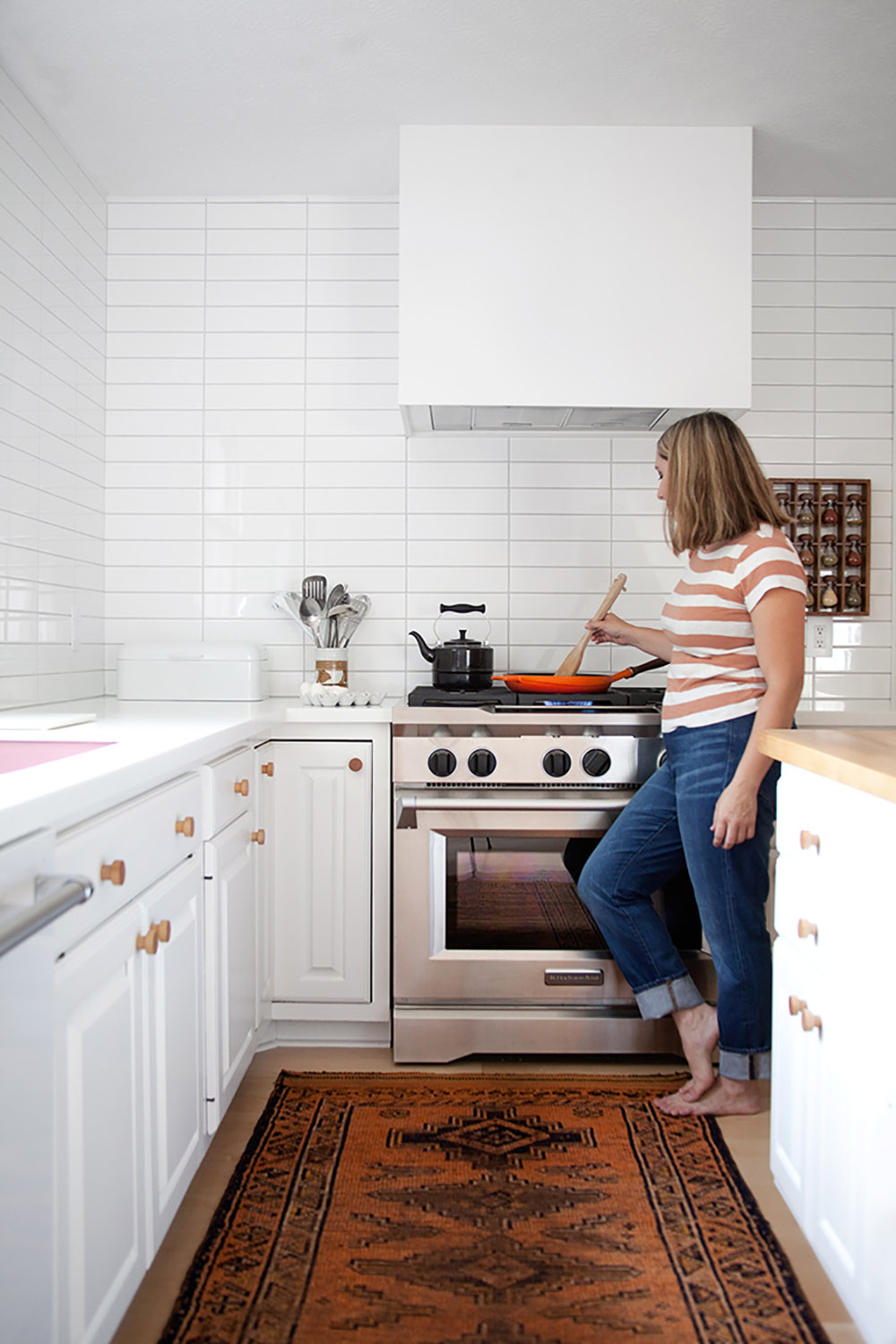 A woman cooking on a gas range.