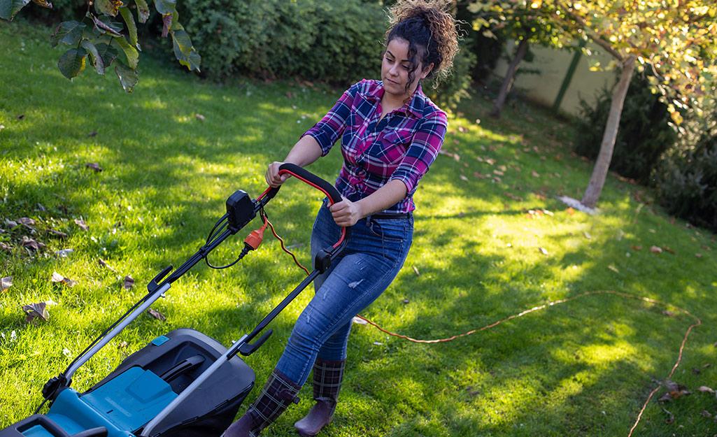A woman mowing a lawn.