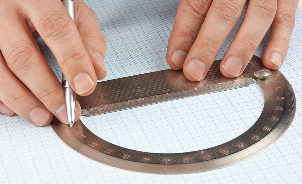 A person holds a metal protractor on top of a piece of graph paper.