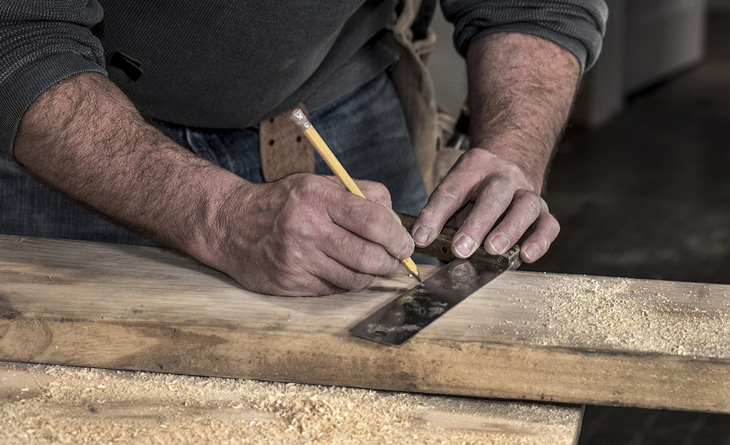 A man uses a hand square and a pencil to mark an angle on a piece of lumber sprinkled with sawdust.