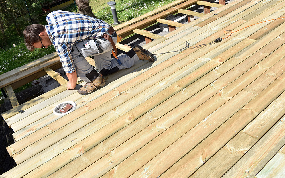 Man measures and plans his wooden deck.