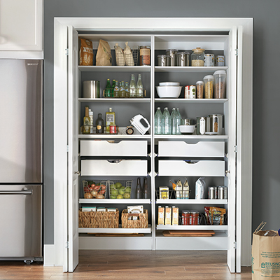 Double doors open to a well-stocked pantry with items on shelves and in drawers.