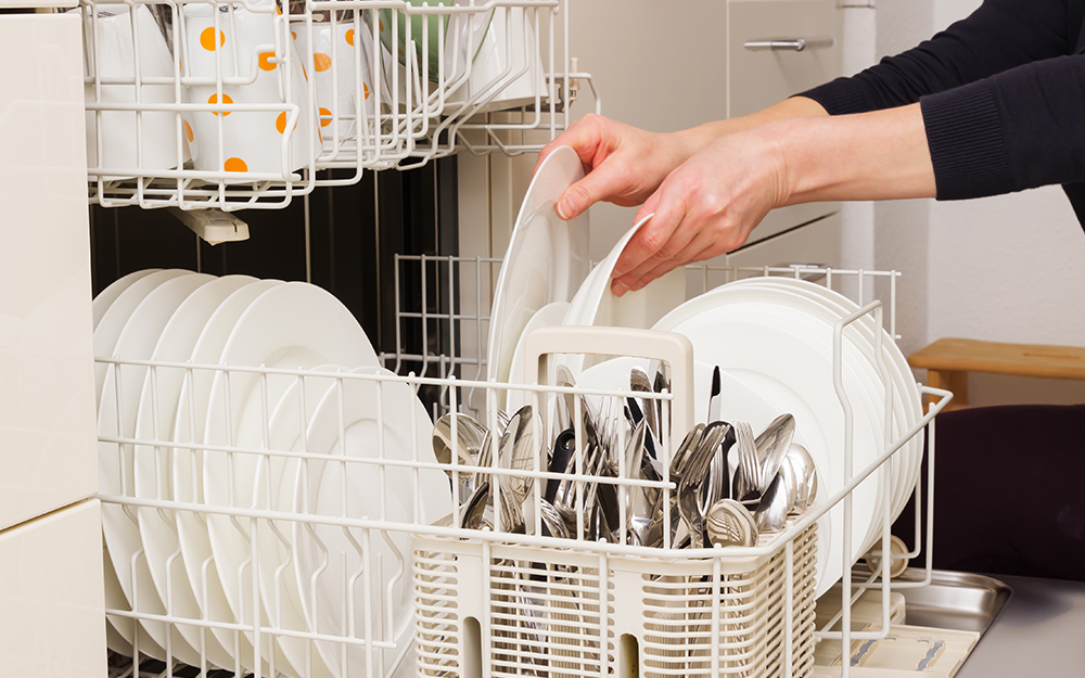 A person empties a dishwasher from the bottom rack first.