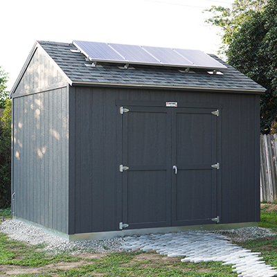 The exterior of a dark colored Tuff Shed with solar panels on the roof.