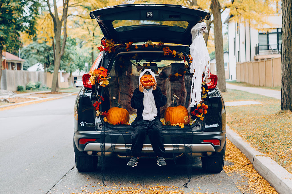 A child sits in the car trunk that's decorated for Halloween.
