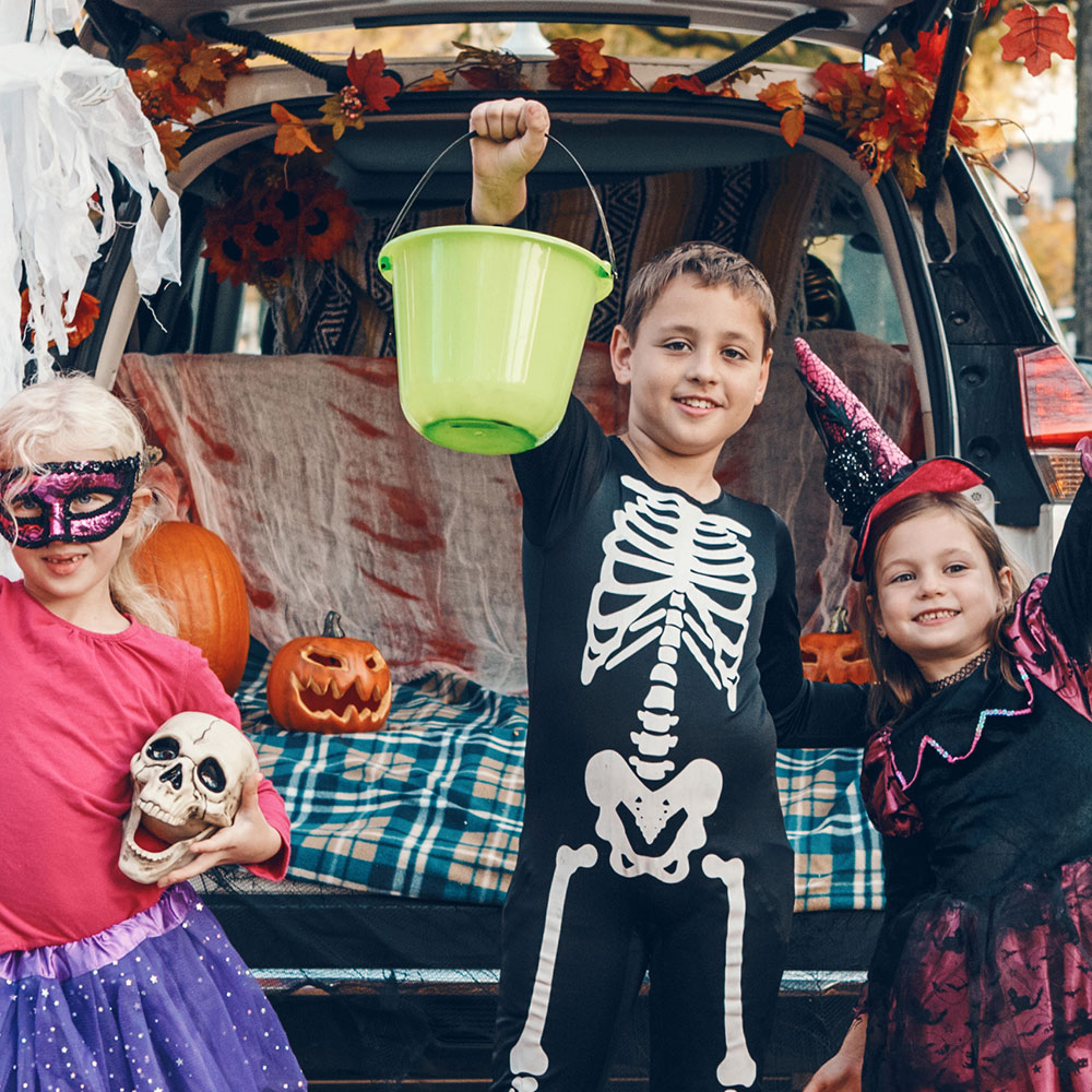 Three costumed kids triumphantly trunk or treating.