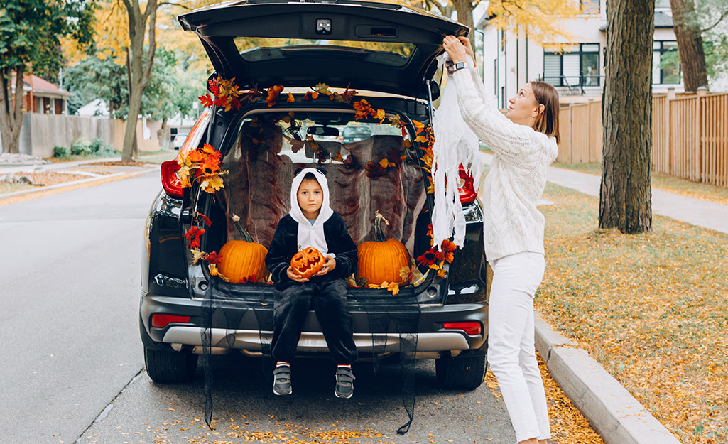 A mom drapes fabric onto a fall trunk or treat car while her child holds a pumpkin.