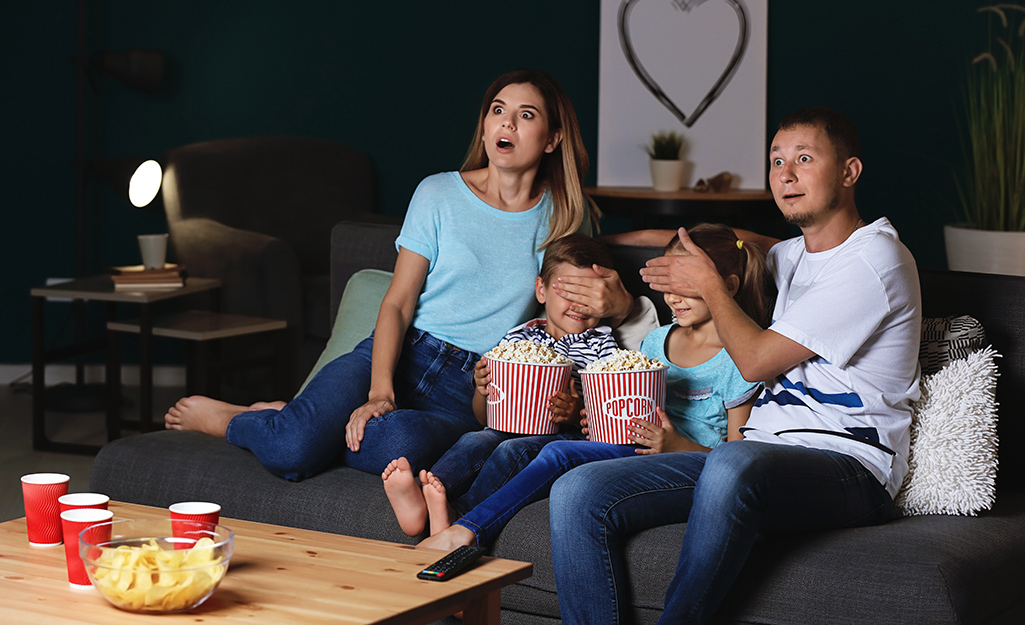 A family watches a scary movie, the parents covering the kids' eyes.