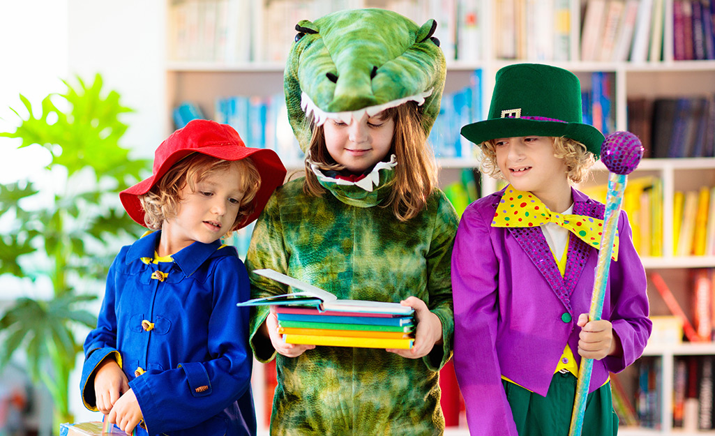 Three kids costumed as book characters wait in the library before trunk or treat.