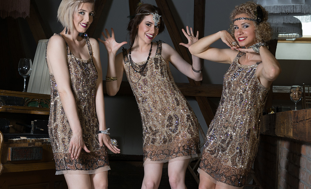 Three people pose in 1920s flapper costumes.