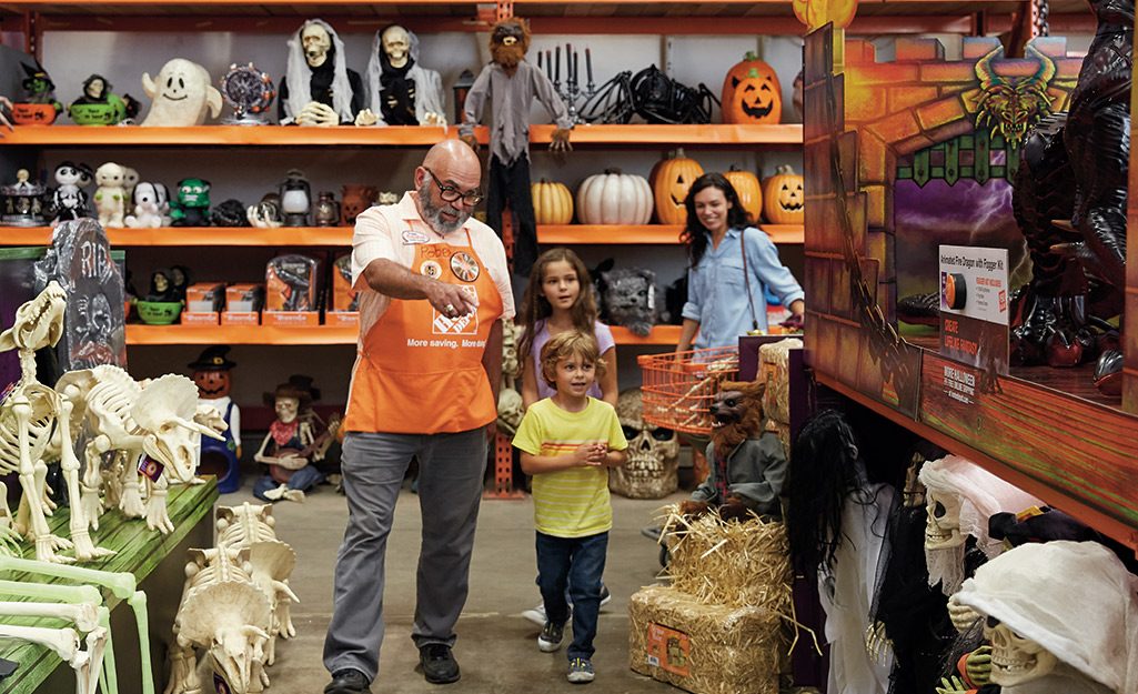 A store associate helps a family shop for trunk or treat decor.