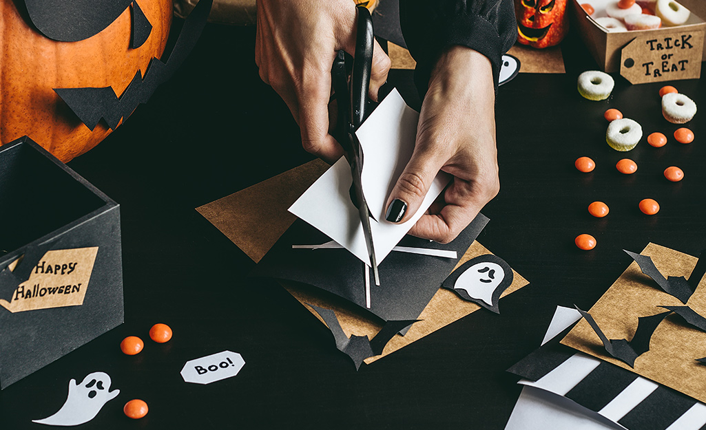 A person trims craft paper for whimsical trunk or treat decorations.