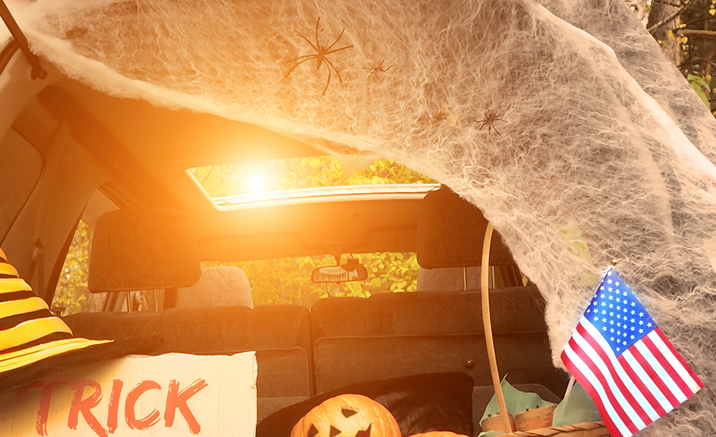 An autumn sun shines through the sunroof of a trunk draped with cobwebs for trunk or treat.