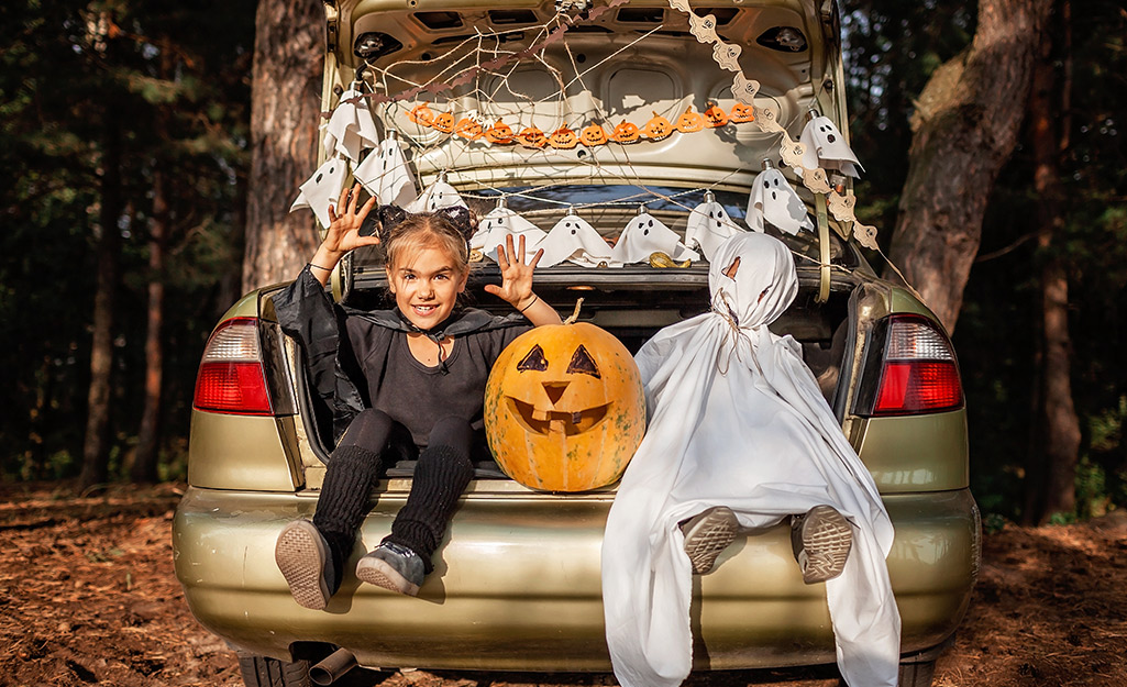 Two kids, dressed as a vampire and a ghost, sit in a trunk or treat trunk with a jack-o'-lantern.