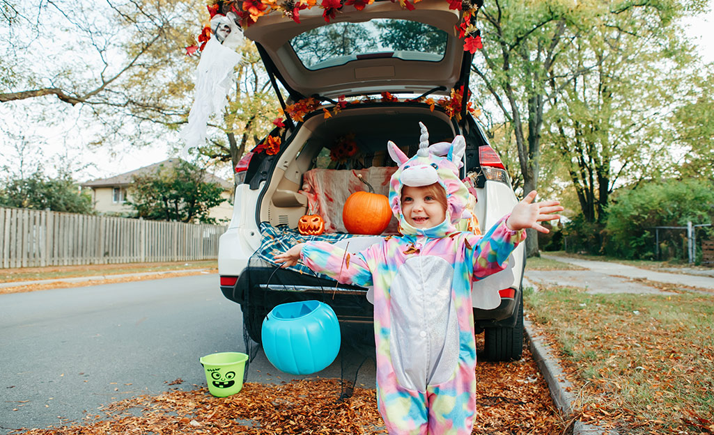 A child in a unicorn costume stands in front of a decorated trunk or treat car.