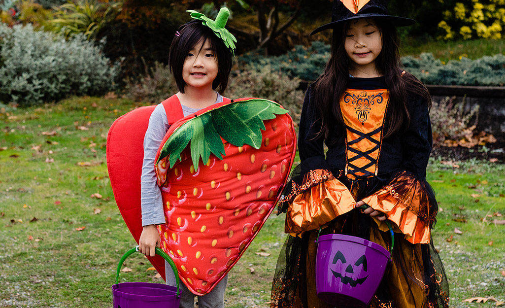 Two kids, dressed as a strawberry and a witch, are ready for trunk or treating.