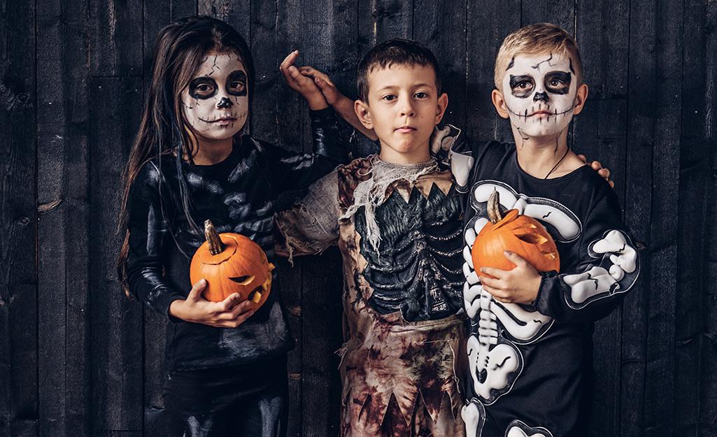 Three kids in skeleton costumes hold small jack-o'-lanterns.