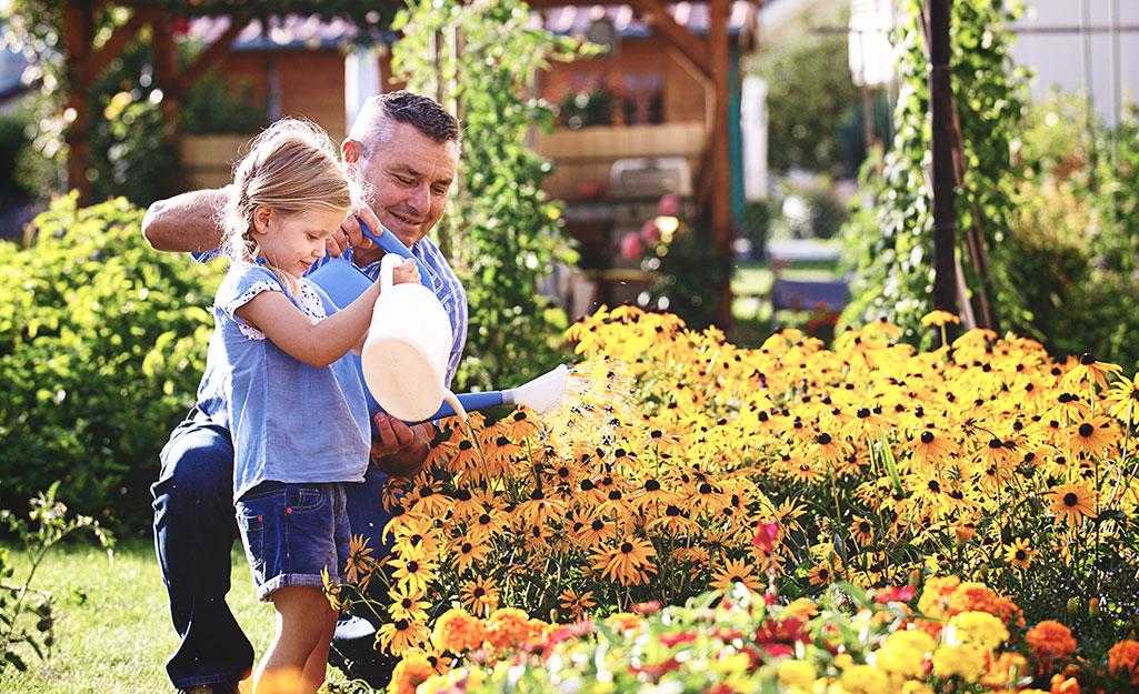A little girl and a man water a summer garden