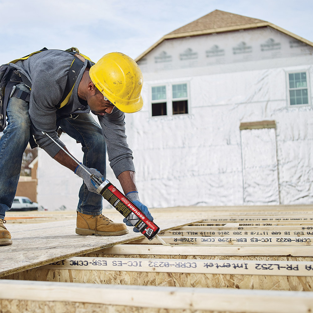 A person uses construction adhesive on a wood joist.