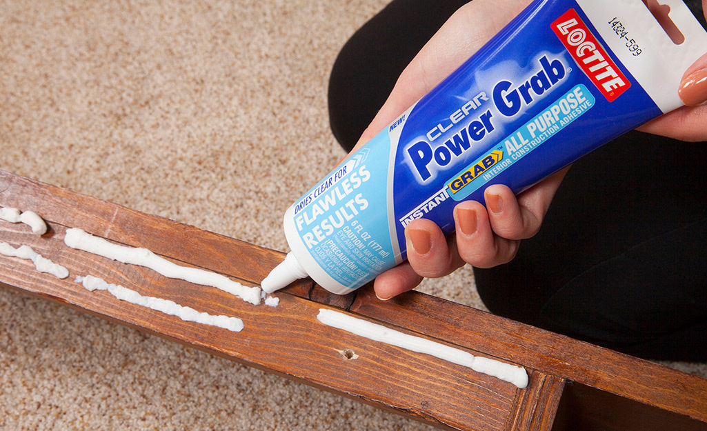 A person uses construction adhesive on a wood slat.