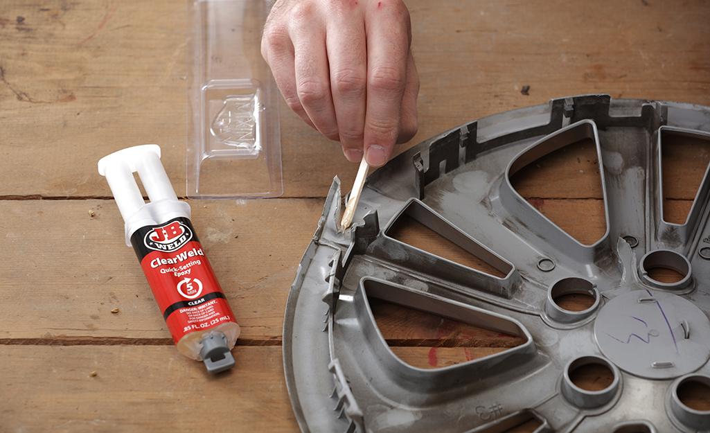 A person uses epoxy on a plastic wheel cover.