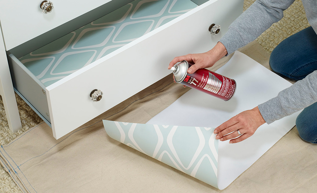 A person uses spray adhesive on a piece of drawer liner paper.