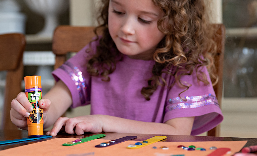 A child uses a glue stick to work on a craft project.