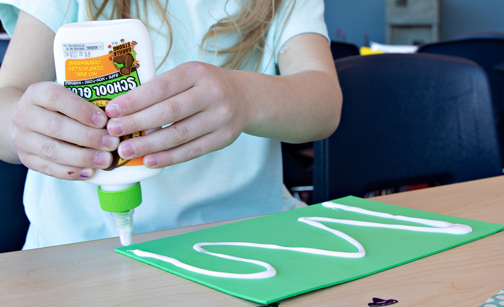 A child using craft glue on construction paper.