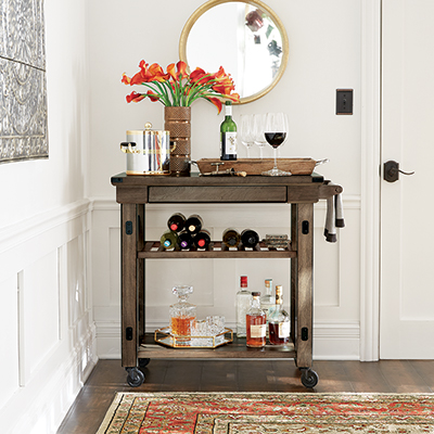 A white wall with stepped baseboards behind a bar cart.
