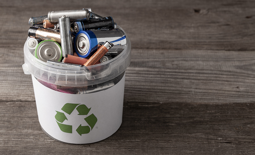 A white bucket with a recycle symbol full of used batteries.