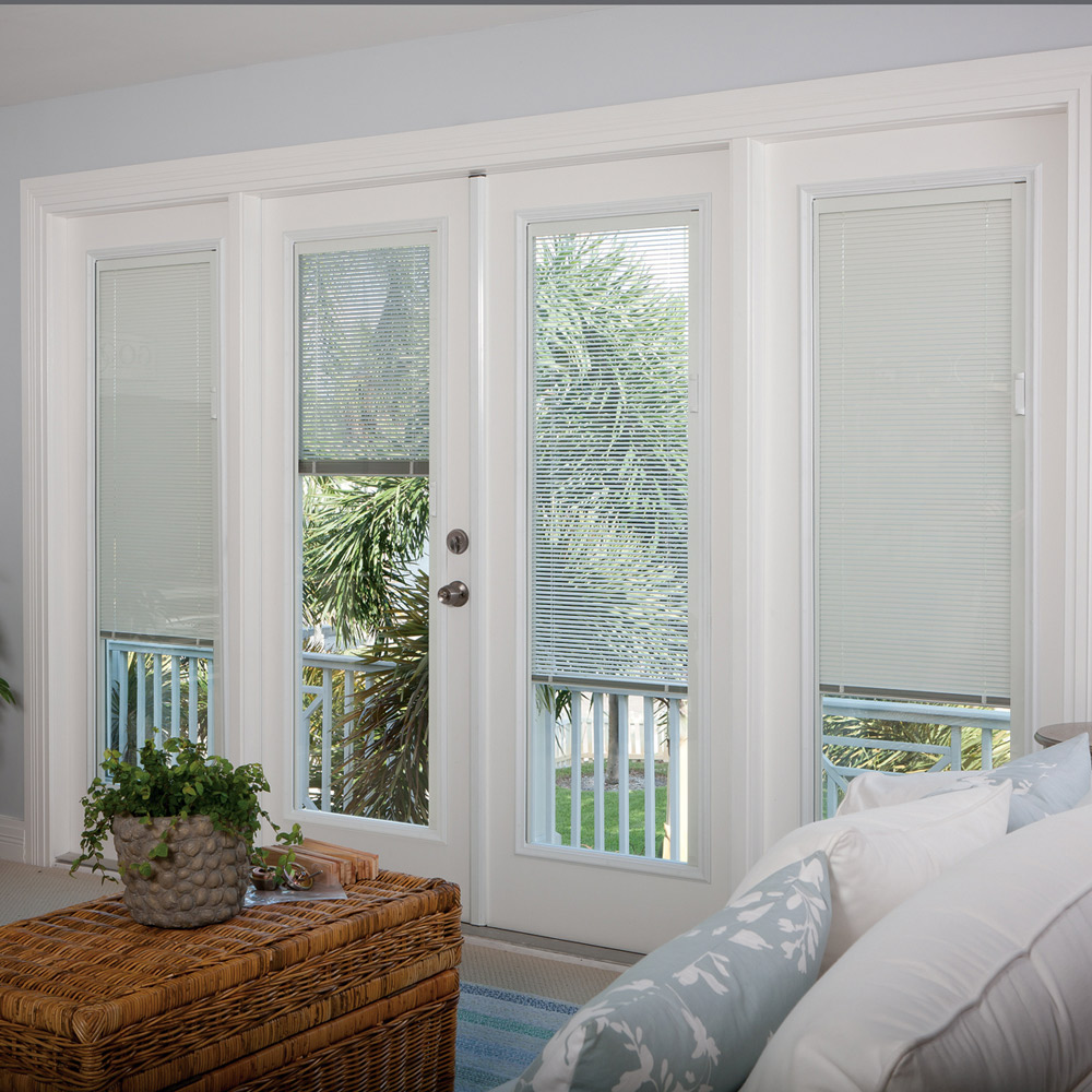 Blinds cover the floor-to-ceiling windows and glass door of a light-filled living room.