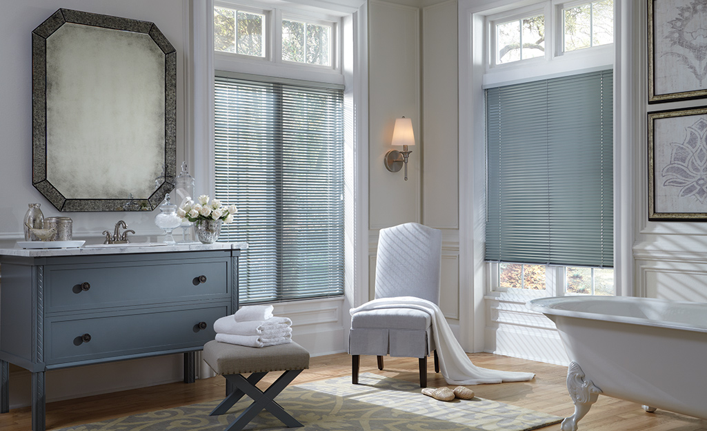 Blue-gray blinds match the color scheme of a large bathroom with a claw-foot tub.