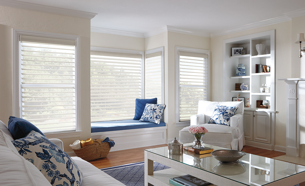 Continuous cord blinds hang in the windows of a comfortable living room with a window seat.
