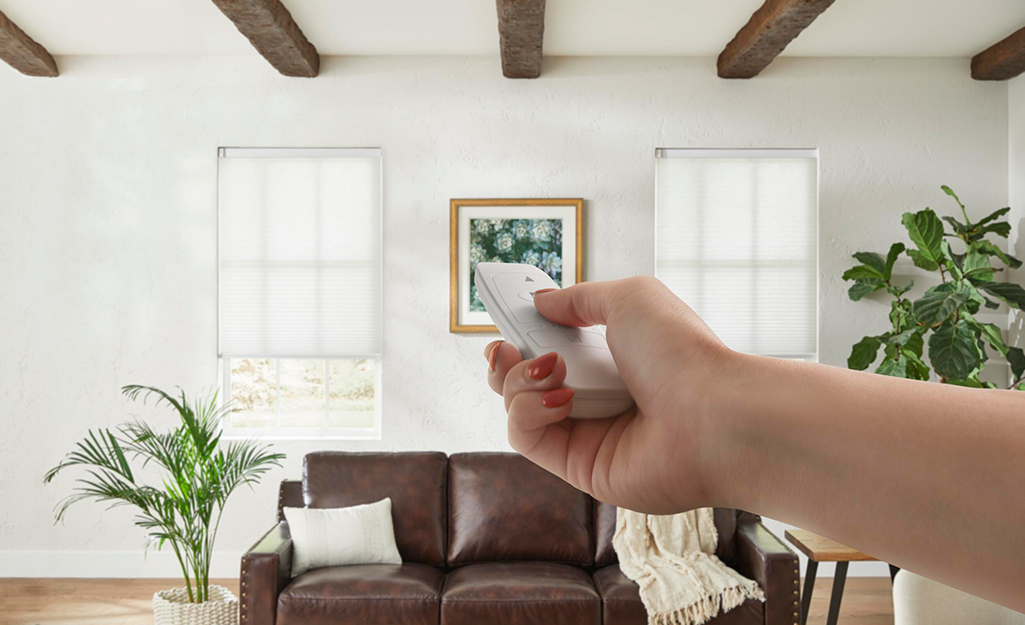 A person uses a remote control to operate motorized blinds.