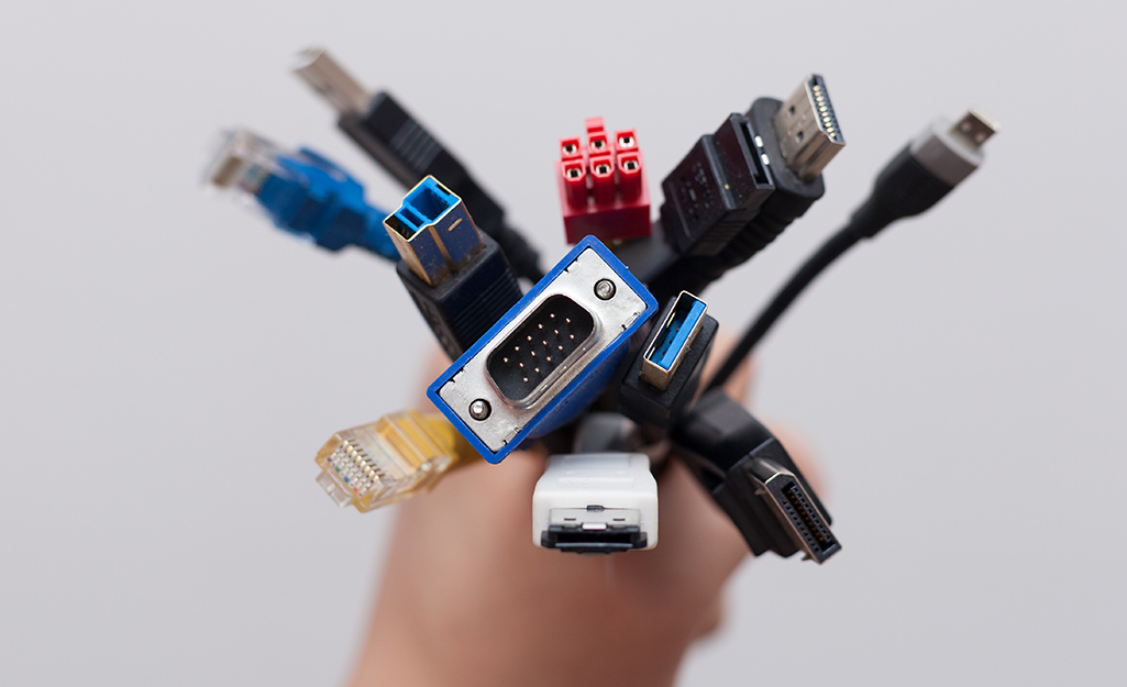 A person holding various cables with different types of connectors.