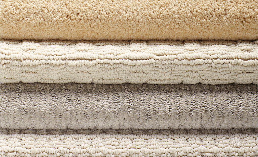 Close up of four rolls of carpeting with different types of fiber sitting atop one another.