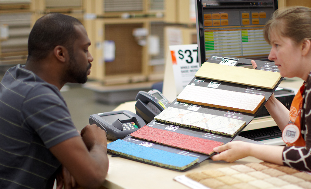A Home Depot employee shows a customer five different samples of carpet padding.